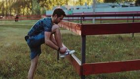 Hombre atlético joven que hace calentamiento antes de ejercicio y que activa metrajes