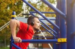 Hombre atlético joven que hace ejercicios del deporte al aire libre en el parque fotos de archivo libres de regalías