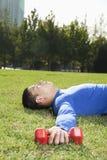 Hombre atlético joven que se acuesta en el parque con pesas de gimnasia, elaboración, vertical Imagen de archivo