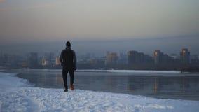 Hombre atlético que corre a la orilla del río del invierno con la opinión del paisaje urbano Logro de la meta almacen de video