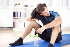Hombre atlético que descansa después de su ejercicio interior fotografía de archivo libre de regalías