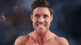 Hombre atlético que dobla sus músculos almacen de metraje de vídeo
