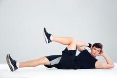 Hombre atlético que hace ejercicios abdominales Imagen de archivo