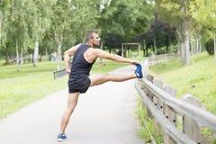 Hombre atlético que hace estiramientos antes de ejercitar, al aire libre foto de archivo libre de regalías
