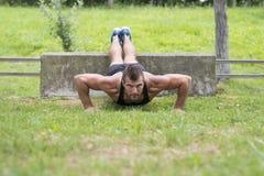 Hombre atlético que hace los pectorales, al aire libre imagenes de archivo
