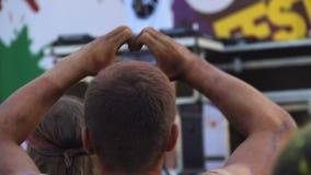 Hombre atlético que muestra la muestra del corazón del amor con las manos y que baila en el concierto de la música almacen de video