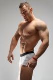 Hombre atlético que presenta sobre fondo gris en blanco Fotos de archivo