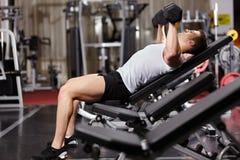 Hombre atlético que trabaja su pecho con pesas de gimnasia pesadas Imágenes de archivo libres de regalías