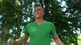 Hombre atlético sano que estira los brazos y el cuello en parque