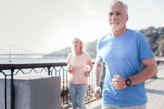 Hombre atlético satisfecho que parece recto y que tiene ejercicios cardiios Imagen de archivo