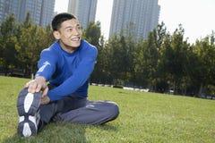 Hombre atlético sonriente de los jóvenes que estira en el parque de Pekín horizontal Foto de archivo
