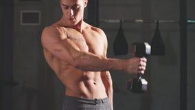 Hombre atl?tico de la aptitud que bombea para arriba los m?sculos con pesas de gimnasia en gimnasio interior metrajes