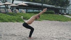 Hombre atl?tico que hace actitud de la yoga y ejercicios de los pilates en la playa arenosa almacen de metraje de vídeo