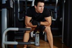 Hombre atlético que toma una rotura después de entrenamiento en el gimnasio Fotos de archivo