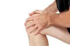 Hombre atractivo adulto en el dolor de lesión del dolor de la rodilla de la ropa de deportes aislado Fotos de archivo libres de regalías