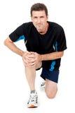 Hombre atractivo adulto en el dolor de lesión del dolor de la rodilla de la ropa de deportes aislado imagen de archivo libre de regalías
