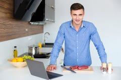 Hombre atractivo con el ordenador portátil que prepara la carne en la cocina Foto de archivo libre de regalías