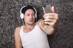 Hombre atractivo con los auriculares infelices hacer el selfie con su m Foto de archivo