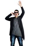 Hombre atractivo con los auriculares que aumentan su mano para arriba mientras que listeni Imagenes de archivo