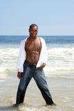Hombre atractivo del afroamericano que presenta en el océano Wate Foto de archivo