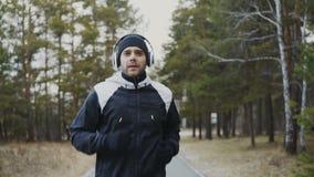 Hombre atractivo del corredor en los auriculares que activan mientras que música que escucha en parque del invierno por la mañana metrajes