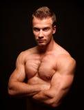 Hombre atractivo deportivo que presenta en gimnasio Imagen de archivo libre de regalías