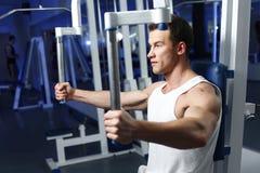 Hombre atractivo deportivo que presenta en gimnasio Foto de archivo libre de regalías