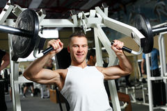 Hombre atractivo deportivo que presenta en gimnasio Fotografía de archivo libre de regalías