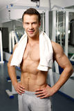 Hombre atractivo deportivo que presenta en gimnasio Imágenes de archivo libres de regalías