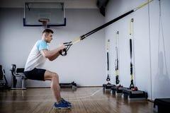 Hombre atractivo durante entrenamiento con las correas de la suspensión en el gimnasio imagenes de archivo