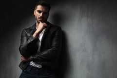 Hombre atractivo en la chaqueta de cuero con el finger en su barbilla foto de archivo libre de regalías