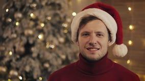 Hombre atractivo en Santa Hat Looking y Smilling en la cámara en fondo del árbol de navidad Cámara lenta metrajes