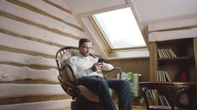 Hombre atractivo en vidrios con el teléfono móvil que se sienta en el ático almacen de metraje de vídeo