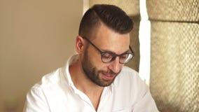 Hombre atractivo en vidrios y en una camisa blanca con un funcionamiento de la barba en la oficina El retrato cercano, baja a su  metrajes