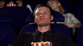 Hombre atractivo feliz que sonríe a la cámara en el cine metrajes