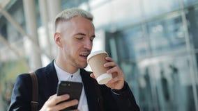 Hombre atractivo feliz sonriente que camina abajo de la calle y que usa smartphone Él café de consumición a ir y lectura buena metrajes