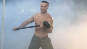 Hombre atractivo fuerte que hace ejercicio con el martillo usando paseo durante el entrenamiento del crossfit en el gimnasio almacen de metraje de vídeo