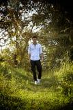 Hombre atractivo hermoso al aire libre en el jardín que se coloca en hierba verde fresca foto de archivo