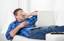Hombre atractivo joven con dolor de cabeza y la tensión usando el ordenador Fotos de archivo libres de regalías