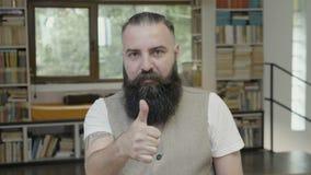 Hombre atractivo joven con la barba que tiene un pulgar encima de la reacción - almacen de metraje de vídeo