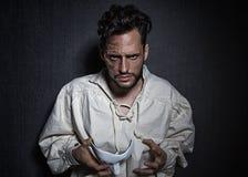 Hombre atractivo joven con las cicatrices de las quemaduras, llevando a cabo un teatro blanco como máscara imágenes de archivo libres de regalías