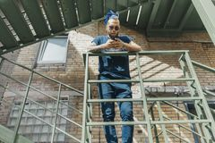 Hombre atractivo joven con los dreadlocks azules que se colocan en la escalera fotos de archivo