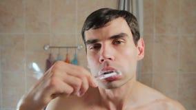 Hombre atractivo joven que cepilla sus dientes que miran en el espejo Individuo que cepilla sus dientes con un cepillo de dientes metrajes