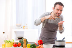 Hombre atractivo joven que cocina en una cocina Fotografía de archivo libre de regalías