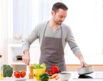 Hombre atractivo joven que cocina en una cocina Imagenes de archivo