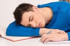 Hombre atractivo joven que duerme en la tabla Fotografía de archivo libre de regalías