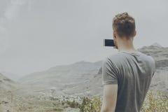 Hombre atractivo joven que hace la imagen de paisaje de la naturaleza con el suyo Foto de archivo libre de regalías