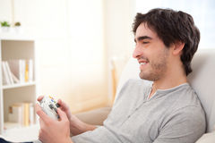 Hombre atractivo joven que juega a los videojuegos en un sofá Fotografía de archivo