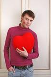 Hombre atractivo joven que lleva a cabo un corazón rojo Fotografía de archivo libre de regalías