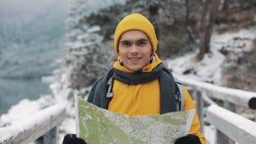 Hombre atractivo joven que lleva el mapa amarillo de la tenencia de la ropa del invierno y que mira en la cámara Retrato de un tu metrajes